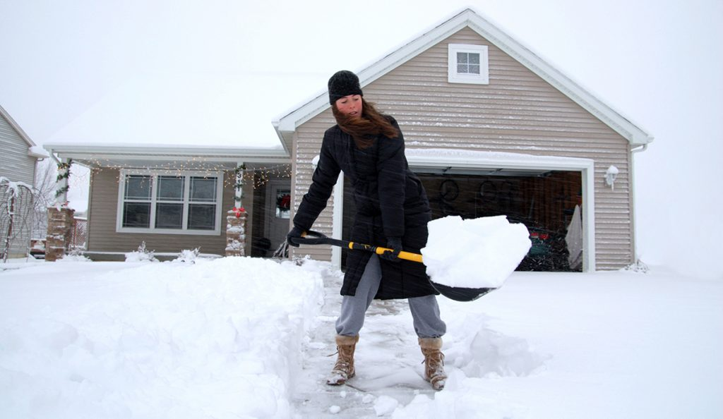 A young woman shovelling her driveway.